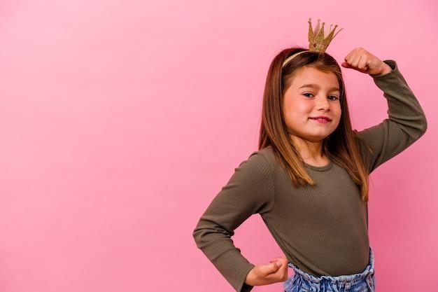 Mała księżniczka dziewczynka z koroną na białym tle na różowym tle podnosząc pięść po zwycięstwie, koncepcja zwycięzca.