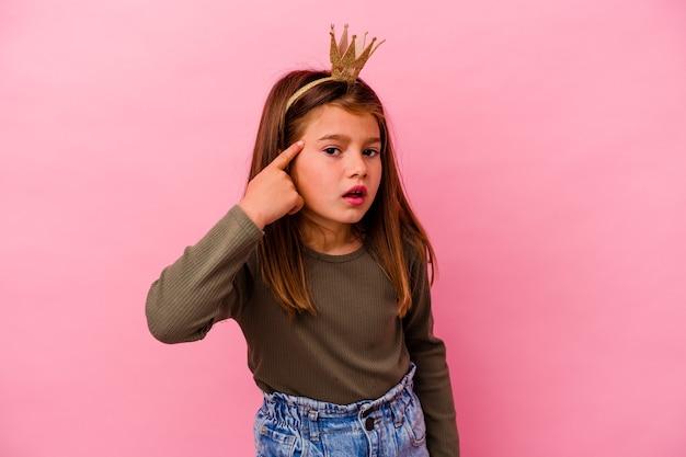 Mała księżniczka dziewczynka z koroną na białym tle na różowym tle pokazując gest rozczarowania palcem wskazującym.