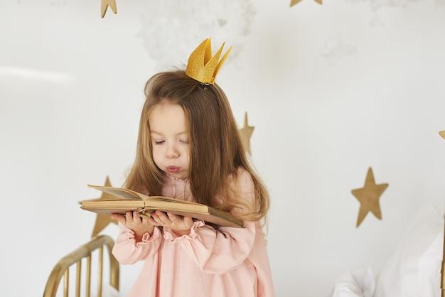 Mała księżniczka z różdżką na łóżku w chmurze na białym tle