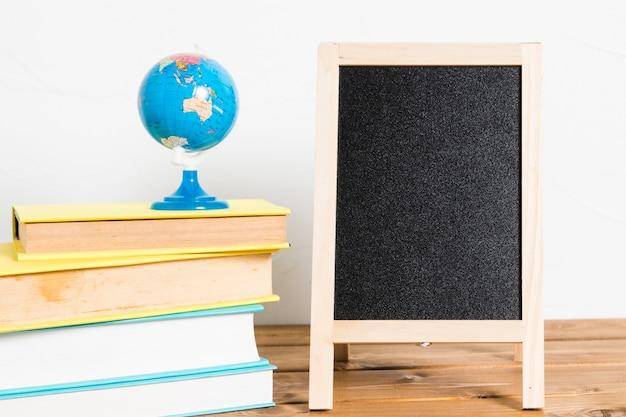Mała kula ziemska na książkach z pustym blackboard na drewnianym stole