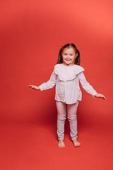 Mała ładna dziewczyna ma dużo zabawy w studio fotograficznym, obrazek na czerwonym tle