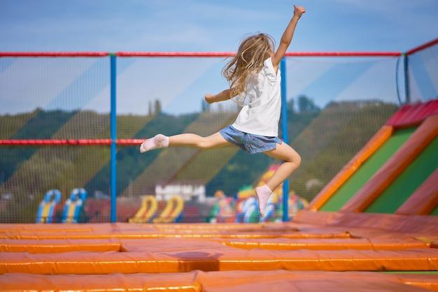 Mała ładna dziewczyna ma zabawę plenerową. skoki na trampolinie w strefie dziecięcej. szczęśliwa dziewczyna skacze na żółtym trampolinie w parku rozrywki