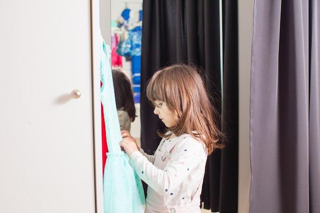 Mała ładna dziewczyna przymierza sukienkę w przymierzalni