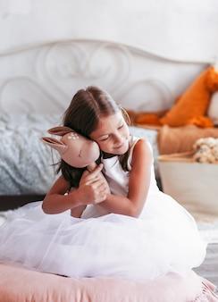 Mała ładna dziewczyna przytula swoją pluszową zabawkę. dziecko siedzi na podłodze w jasnym pokoju