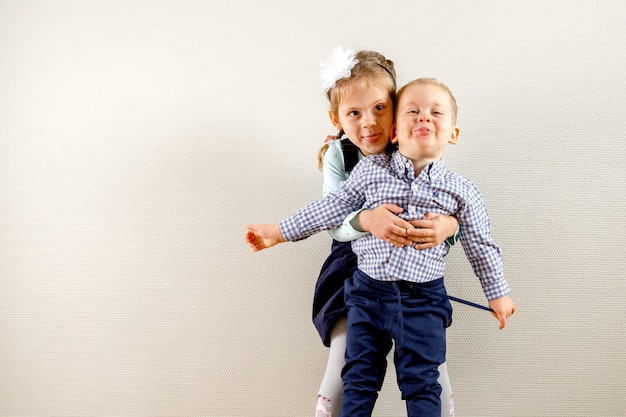 Mała ładna dziewczyna stojąca obok brata i przytulająca go, podczas gdy oboje są uśmiechnięci i szczęśliwi