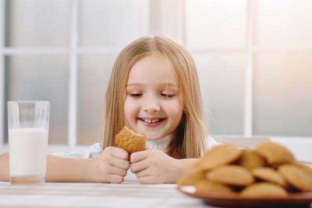 Mała ładna dziewczyna uśmiecha się podczas jedzenia słodkiego ciasteczka