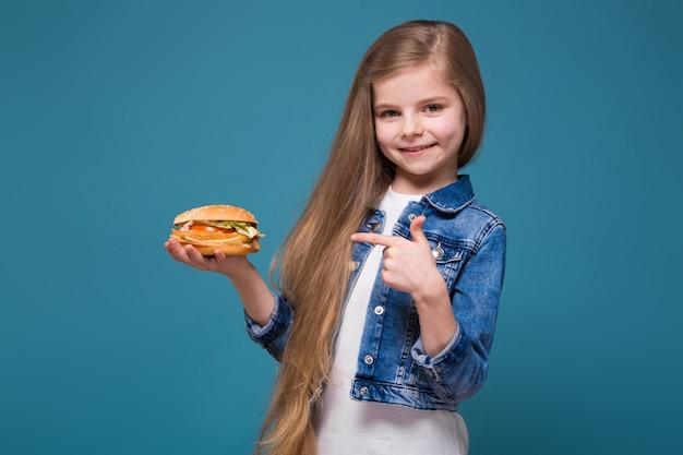 Mała ładna dziewczyna w dżinsowej kurtce z długimi brązowymi włosami trzyma burgera
