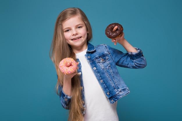 Mała ładna dziewczyna w dżinsowej kurtce z długimi brązowymi włosami trzyma ciasto