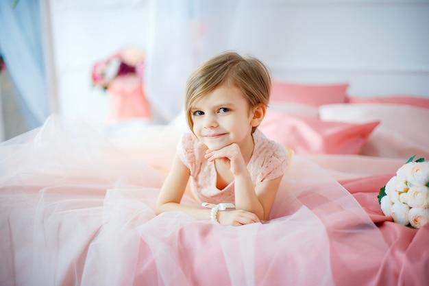 Mała ładna dziewczyna w sukni lying on the beach na łóżku z kwiatami
