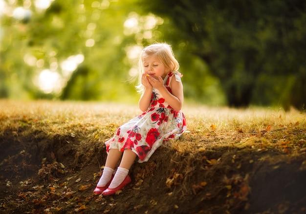 Mała ładna dziewczyna w sukni z makiem dmucha liść przy wzgórzem. skopiuj miejsce