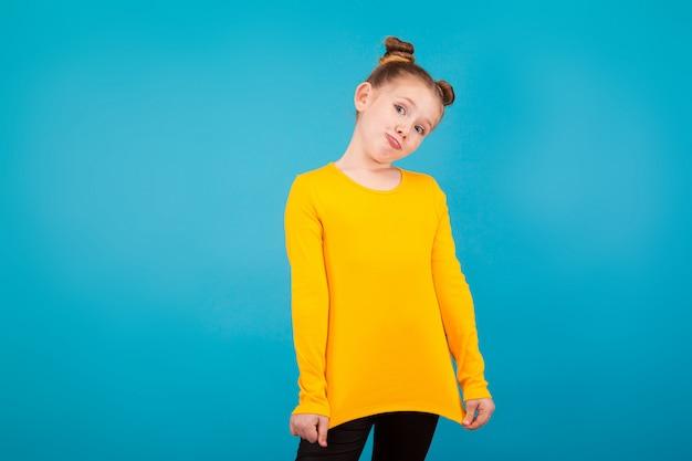 Mała ładna dziewczyna w żółtej koszuli