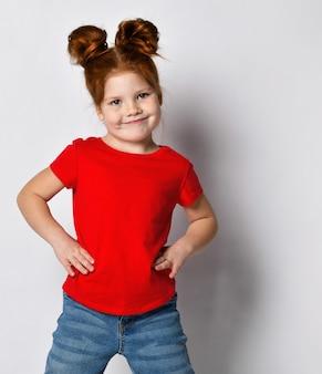 Mała ładna dziewczyna z rudymi włosami i piegami trzyma ręce na talii i odwraca wzrok. dziecko w czerwonej koszulce i dżinsach pozuje na tle szarej ściany w studio.