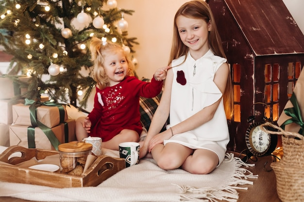 Mała ładna dziewczynka sith z falującymi włosami siedzi z pudełkiem z prezentem i raduje się ze starszą siostrą