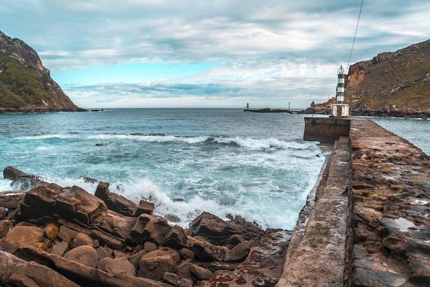 Mała latarnia morska na kamiennym molo w pasajes san pedro, gipuzkoa, hiszpania