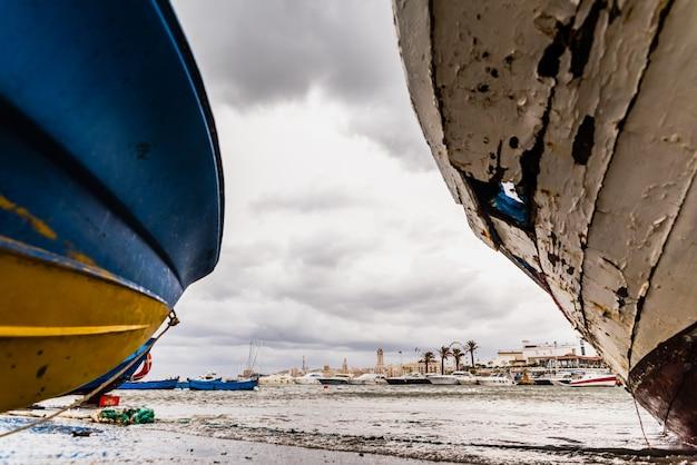 Mała łódka cumująca bari port, włochy, podczas burzy przy morzem.