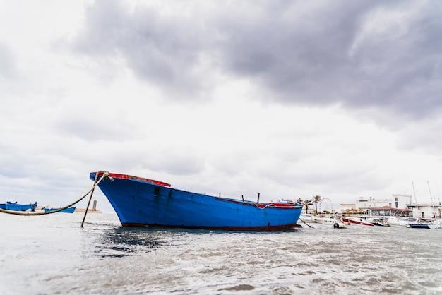 Mała łódka cumująca do portu bari, włochy, podczas burzy na morzu.