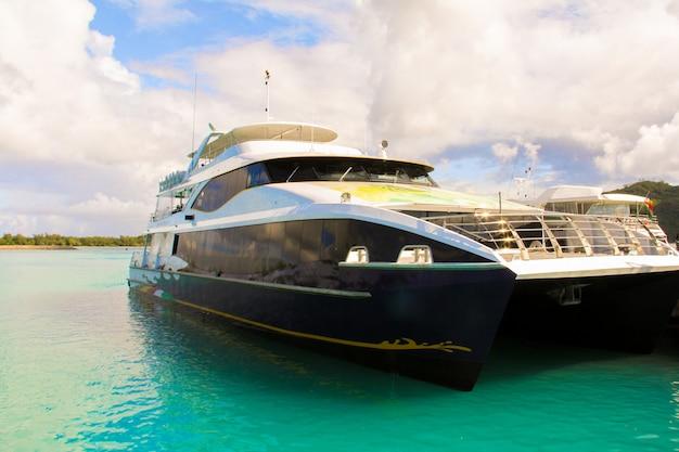 Mała łódka i krążownik u wybrzeży tropikalnej wyspy w turkusowej wodzie
