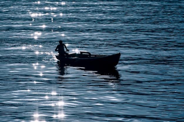 Mała łódka na jeziorze w sylwetce z odbijającymi promieniami słońca