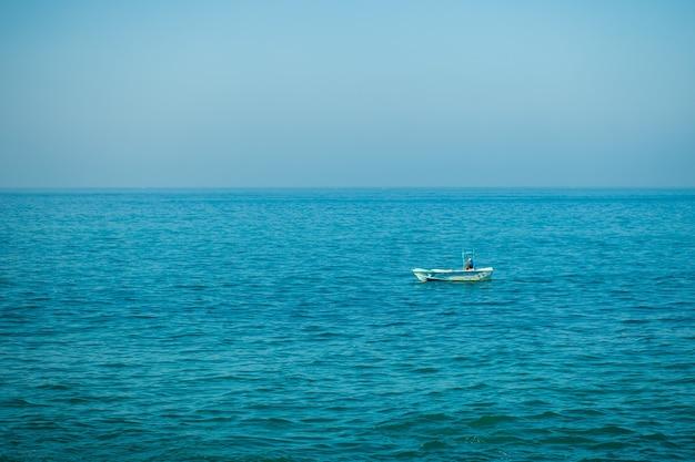 Mała łódka na spokojnym oceanie morskim