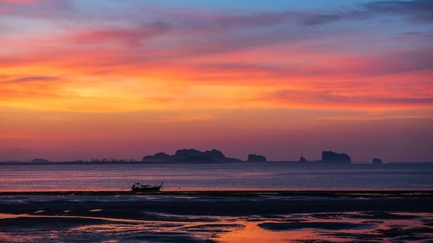 Mała łódka w morzu z mrocznym niebem w ranku przy koh mookiem, trang prowincja, tajlandia