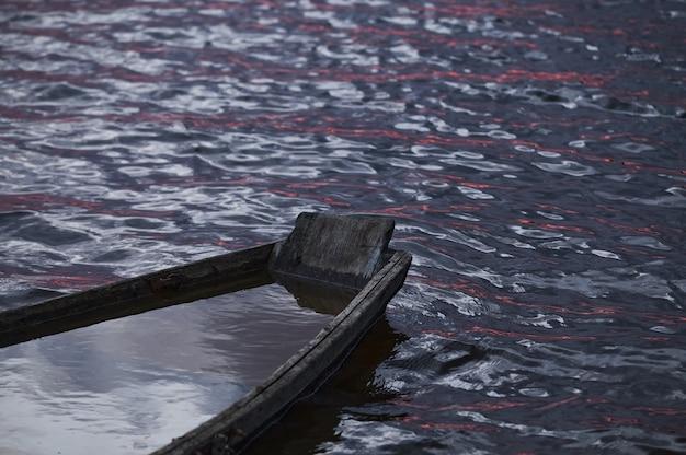 Mała łódka zatonęła w wodzie nocnego zachodu słońca