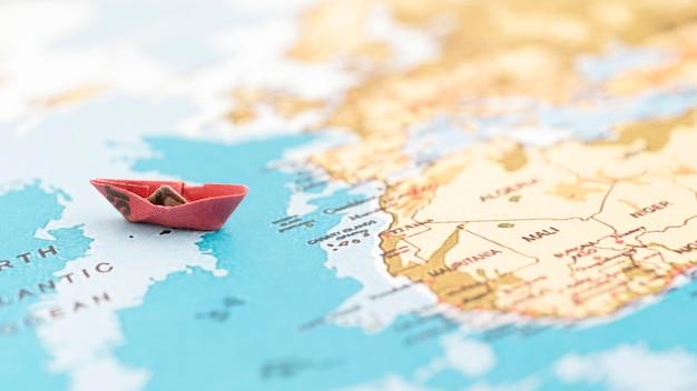 Mała łódź na mapie świata pod dużym kątem