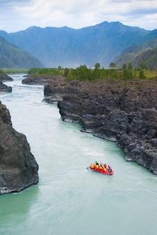 Mała łódź raftingowa w rwącej górskiej rzece wśród skał