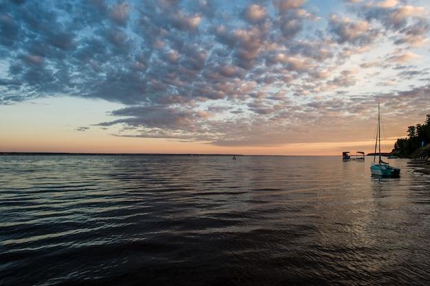 Mała łódź rybacka na plaży z zmierzchem w ranku