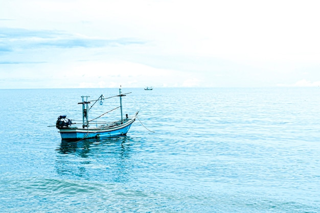 Mała łódź rybacka unosząca się w błękitnym morzu z błękitnym niebem, tajlandia łódź rybacka lub łódź rybacka lub statek na plaży sam roi yod prachuap khiri khan tajlandia z błękitnym niebem, chmurami i błękitnym morzem