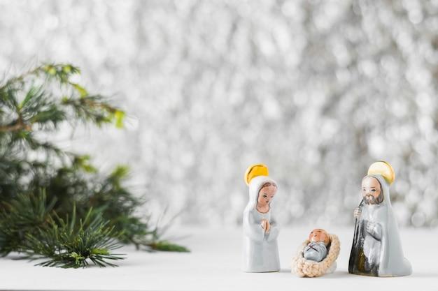Mała maryja dziewica z dzieciątkiem jezus i świętego józefa w pobliżu choinki