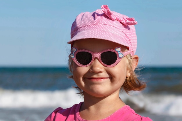Mała marzycielska dziewczynka w kolorze różowym w okularach przeciwsłonecznych na tle morskich fal i nieba