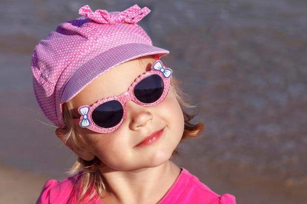 Mała marzycielska dziewczynka w kolorze różowym z zamkniętymi oczami w okularach przeciwsłonecznych na tle wody na piasku