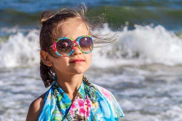 Mała marzycielska dziewczynka z zamkniętymi oczami w okularach przeciwsłonecznych, w których odbija się słońce na morzu