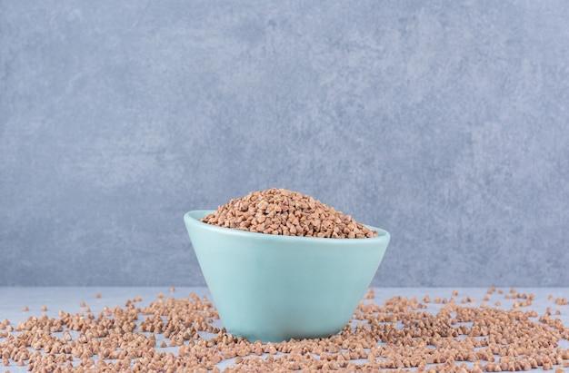 Mała miska gryki umieszczona w środku rozsypanych ziaren na marmurowej powierzchni