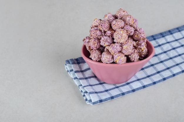 Mała miska na starannie złożonym ręczniku, zawierająca hojną porcję popcornowych cukierków na marmurowym stole.
