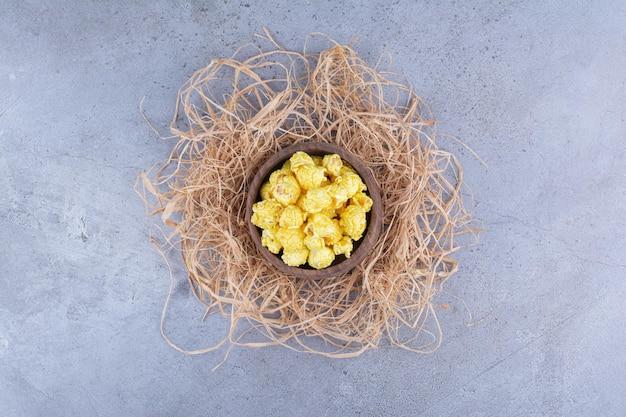 Mała miska na szczycie słomy wypełniona popcornem pokrytym cukierkiem na marmurowej powierzchni