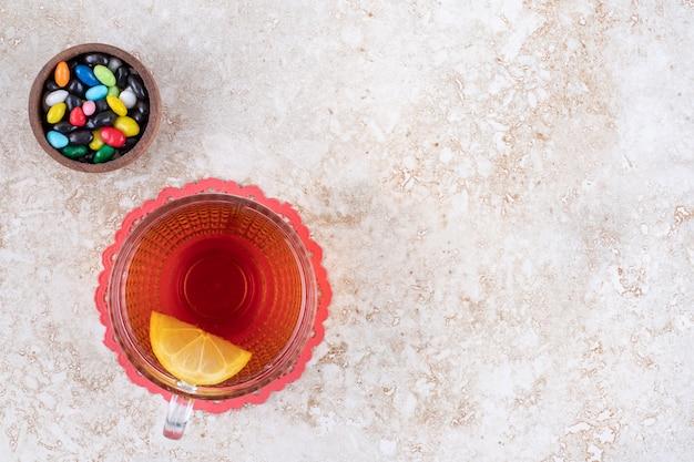Mała miska różnych cukierków i filiżanka herbaty