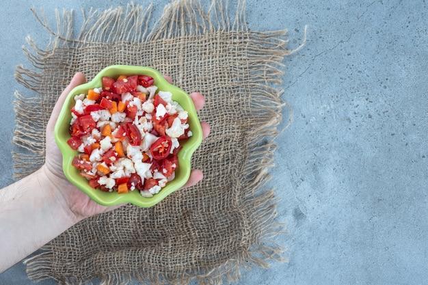 Mała miska w dłoni, wypełniona sałatką z kalafiora i papryki na marmurowym stole.
