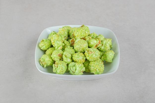 Mała miska zielonego kandyzowanego popcornu na marmurowym stole.