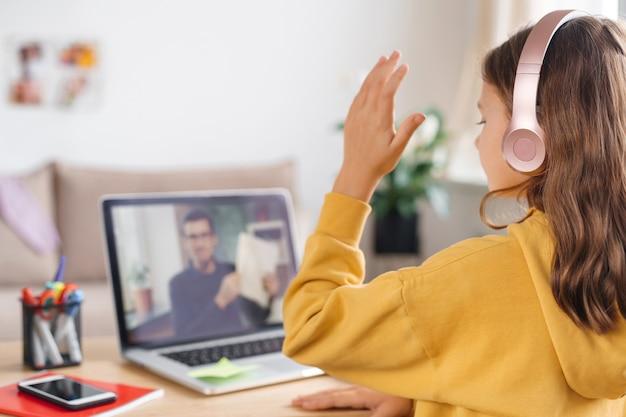 Mała młoda dziewczyna w szkole domowej uczy się wirtualnej klasy internetowej online od nauczyciela szkolnego na zdalnym spotkaniu z powodu pandemii zakaźnej