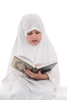 Mała młoda muzułmańska dziewczyna czyta koran