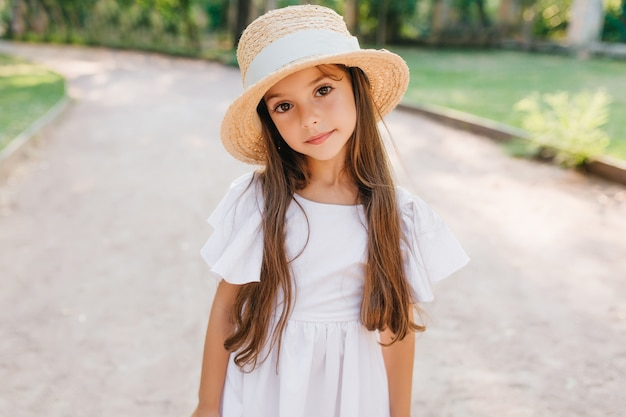 Mała modna dama z długimi rzęsami patrząc z zaciekawieniem stojąc na drodze w eleganckim kapeluszu. zewnątrz portret nieśmiała dziewczyna brązowowłosa na sobie śliczną białą suknię.