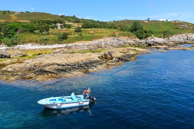 Mała motorówka zaparkowana wzdłuż brzegu z dużymi skałami i przejrzystą wodą.