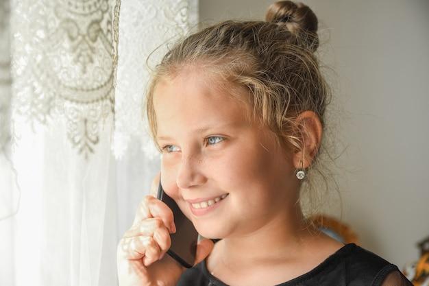 Mała nastolatka przy oknie rozmawia przez telefon.