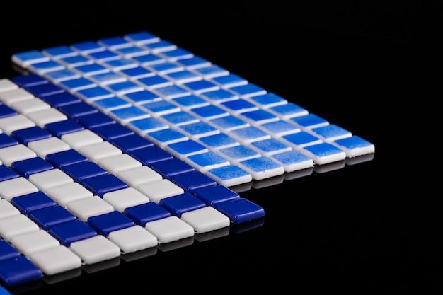 Mała niebieska płytka ceramiczna na czarnym tle, majolika. do katalogu