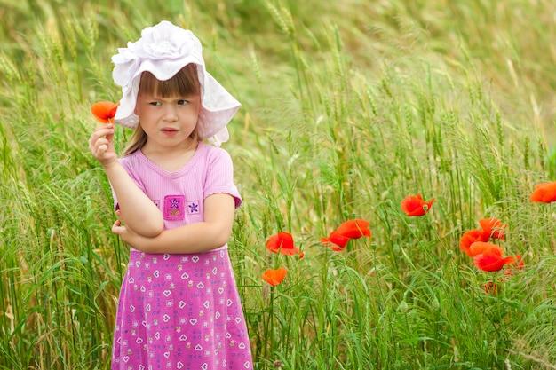 Mała niezadowolona i niezadowolona śliczna dziewczyna z czerwonym kwiatem