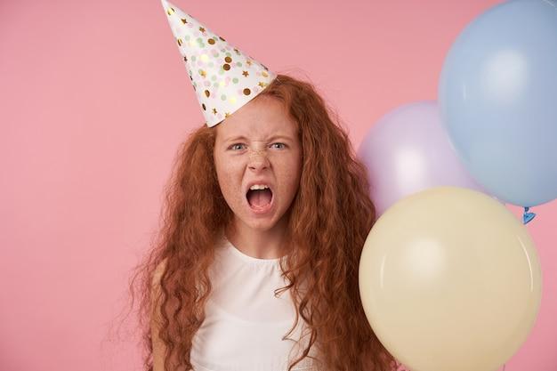 Mała niezadowolona, kręcona dziewczyna z długimi włosami krzycząca ze złością i marszcząca brwi, pozująca na różowym tle z kolorowymi balonami, będąca w złym nastroju, ubrana w białą sukienkę i czapkę urodzinową