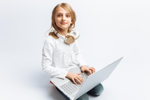 Mała nowoczesna dziewczyna siedzi z laptopem i słuchanie muzyki, słodkie i piękne