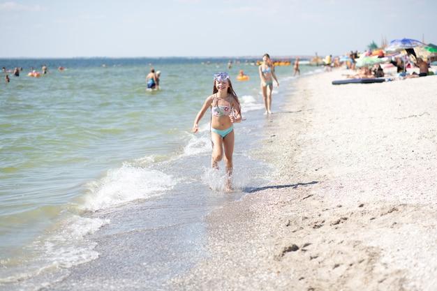 Mała opalona dziewczynka z długimi włosami w niebieskim kostiumie kąpielowym biegnie wesoło po piaszczystym brzegu w pobliżu morza czarnego