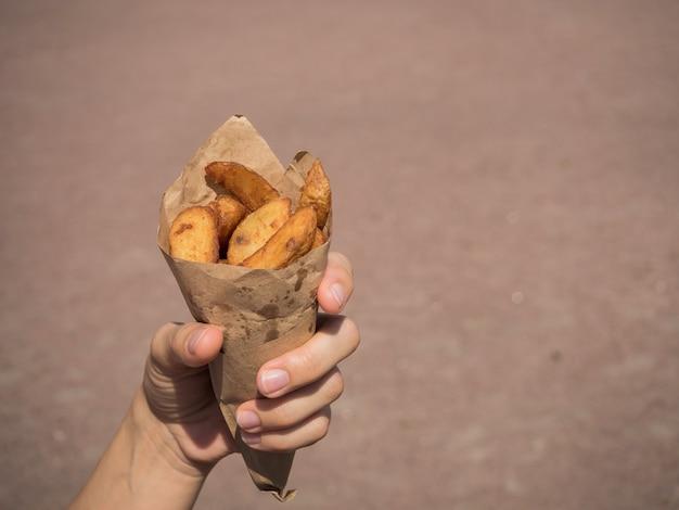 Mała paczka frytek ziemniaczanych, szybka przekąska na ulicy.